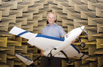 Professor Colin Hansen with a model aircraft in the School of Mechanical Engineering's anechoic chamber