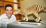 Dr Jeremy Austin with a mounted specimen of a baby thylacine from the SA Museum