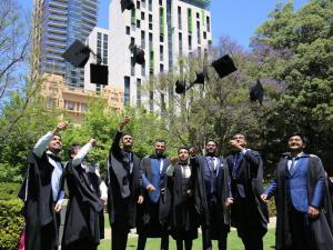 Graduates on lawn throwing caps