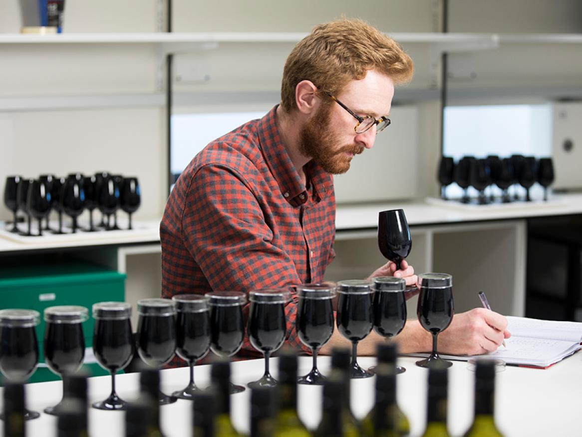 man trying wine in a wine lab