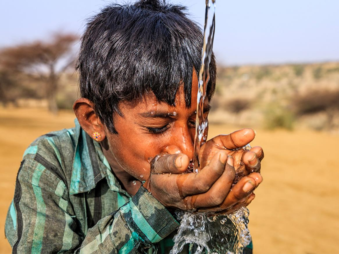 Photo of young boy drinking water in the desert region of Rajasthan, India