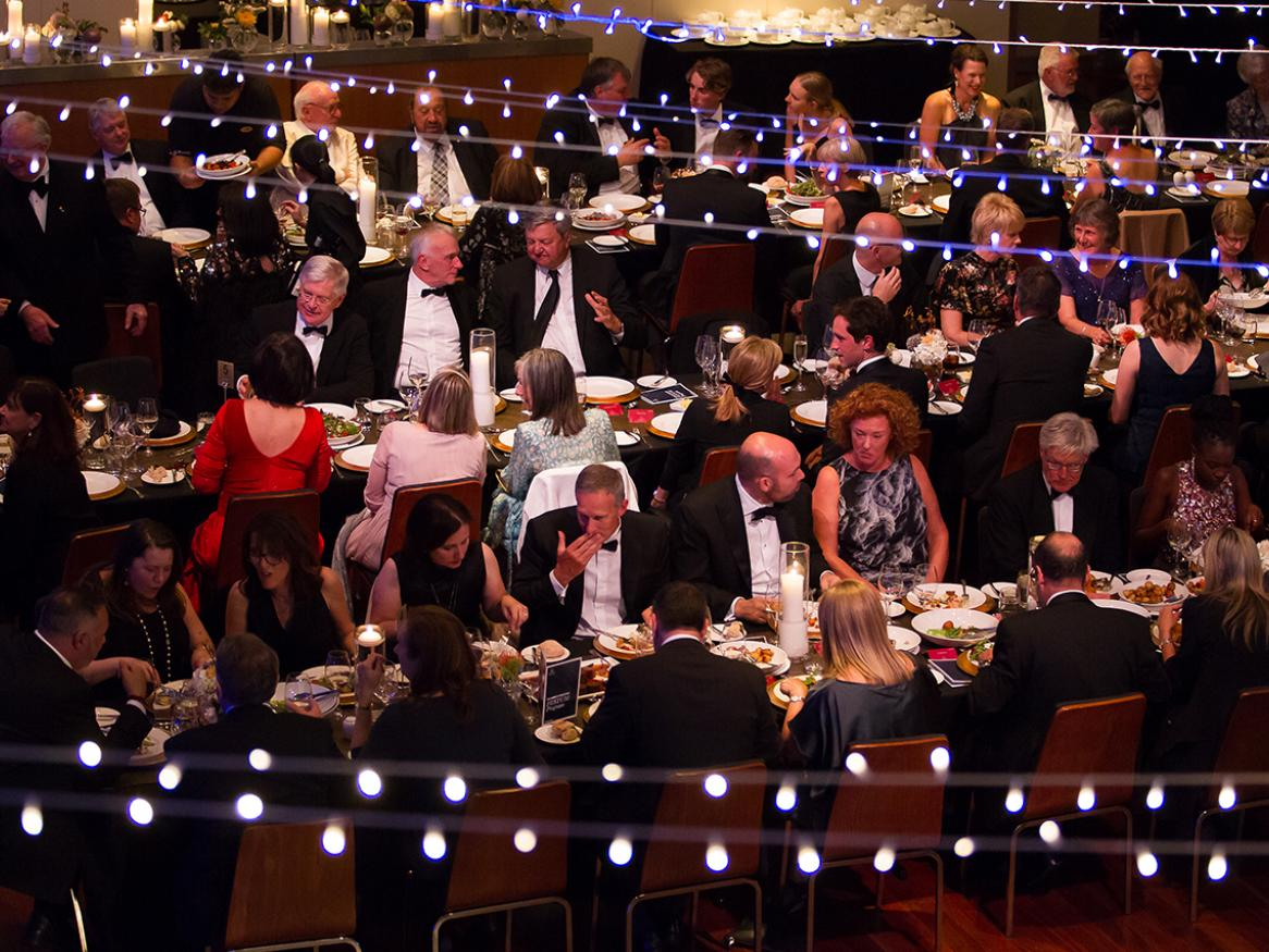 A photo from the inaugural Board of Benefactors Festum which shows people sitting on long tables under festoons of lights