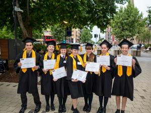 Students outside with graduation certificates