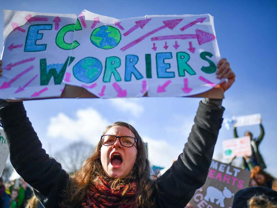 Girl holding up sign that says eco-worrier