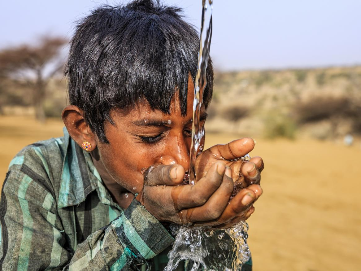 Photo of a young boy drinking water in the deserts of Rajasthan
