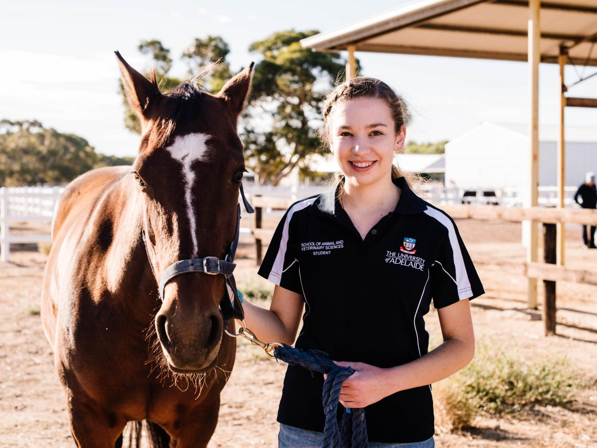 Female student standing with a horse at the University's Roseworthy campus.
