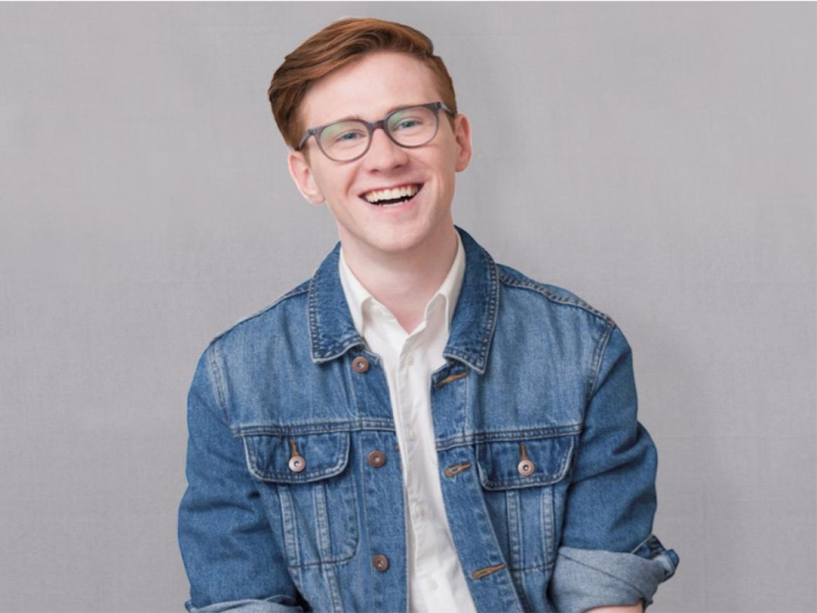 Young male student is smiling at the camera, wearing glasses and a denim jacket.