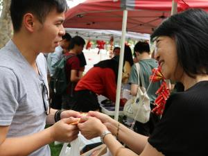 Professor Jacqueline Lo (PVCI) handing money packets (with chocolate coins) to Oscar Ong, SRC President