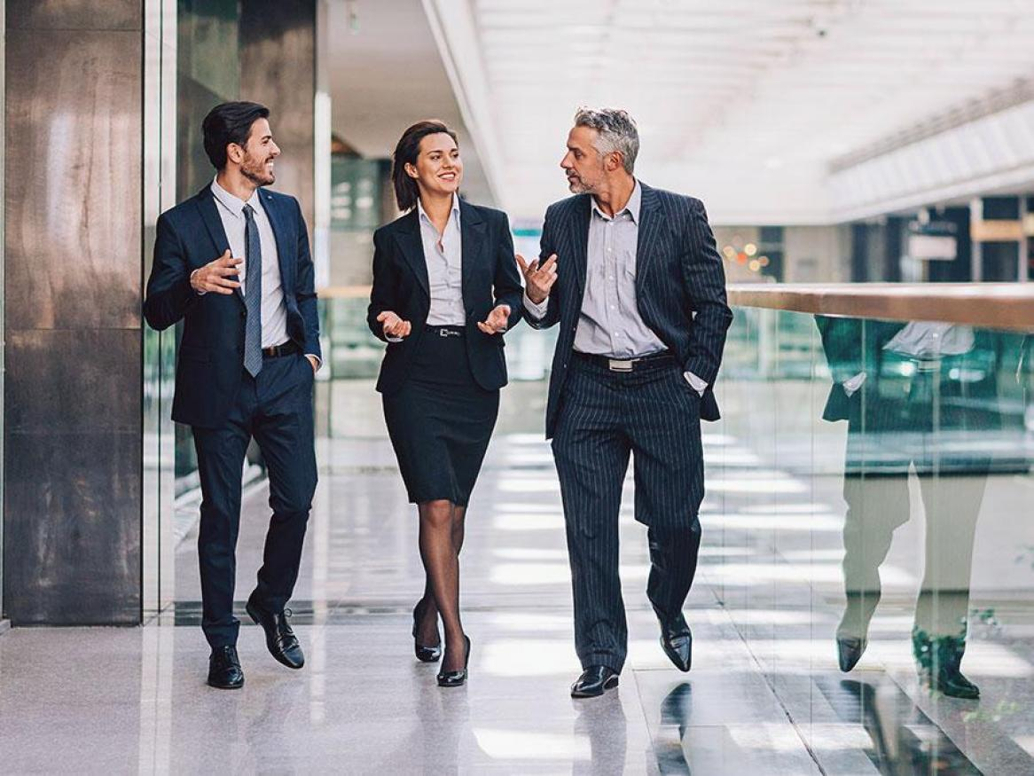 An image of 3 professionals walking in a corporate setting