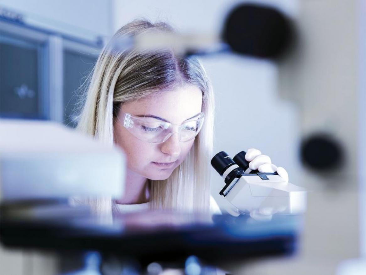 A photo of a girl looking at a research lab looking through a microscope