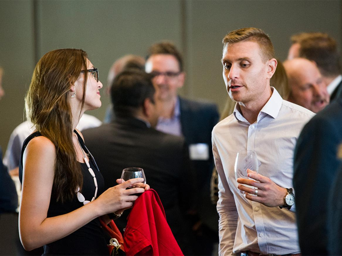 A photo of two people chatting at an industry event