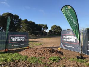 Photo of University banners in front of the location of the Roseworthy Solar Farm