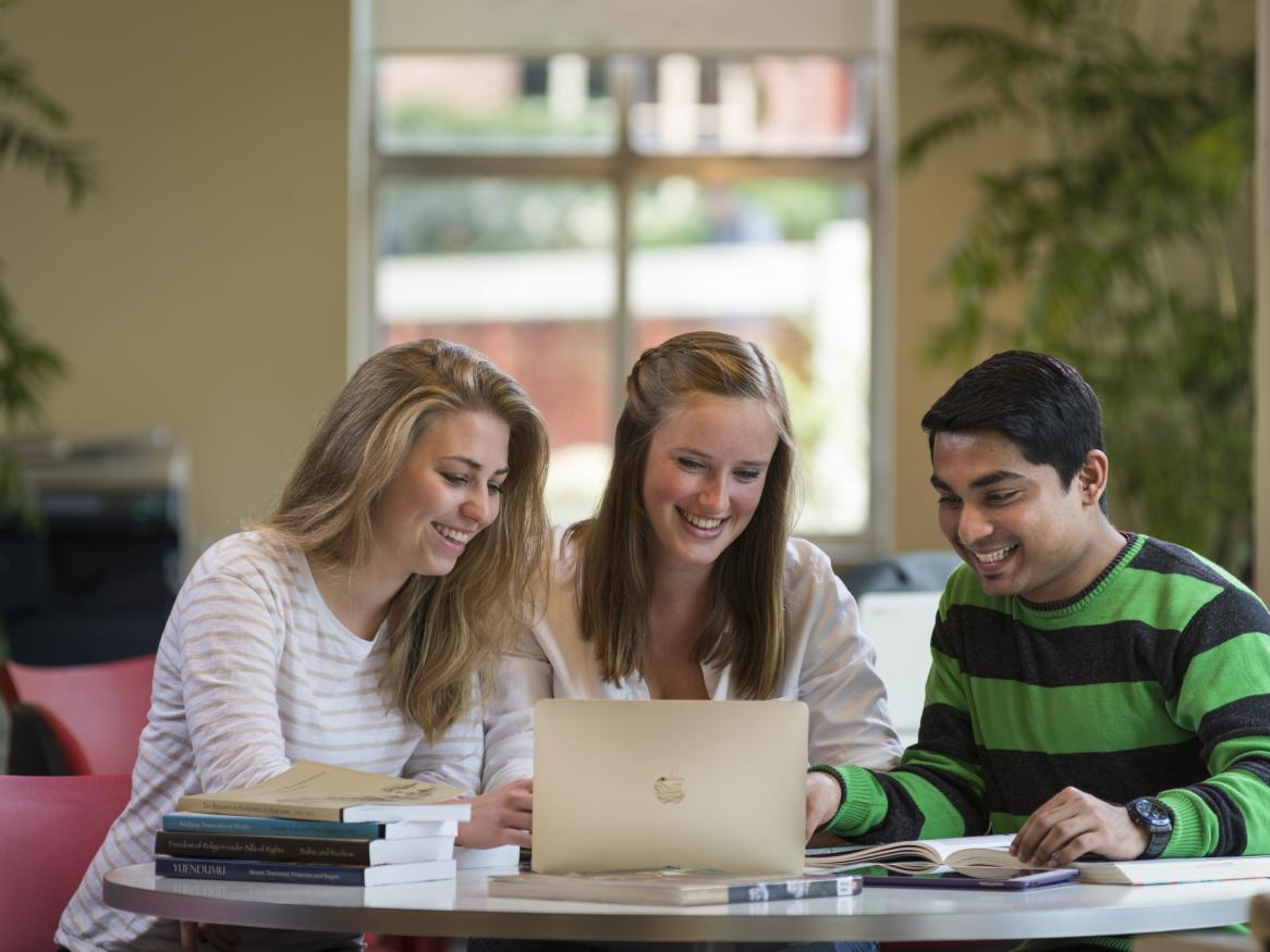 Three happy students studying together in the library