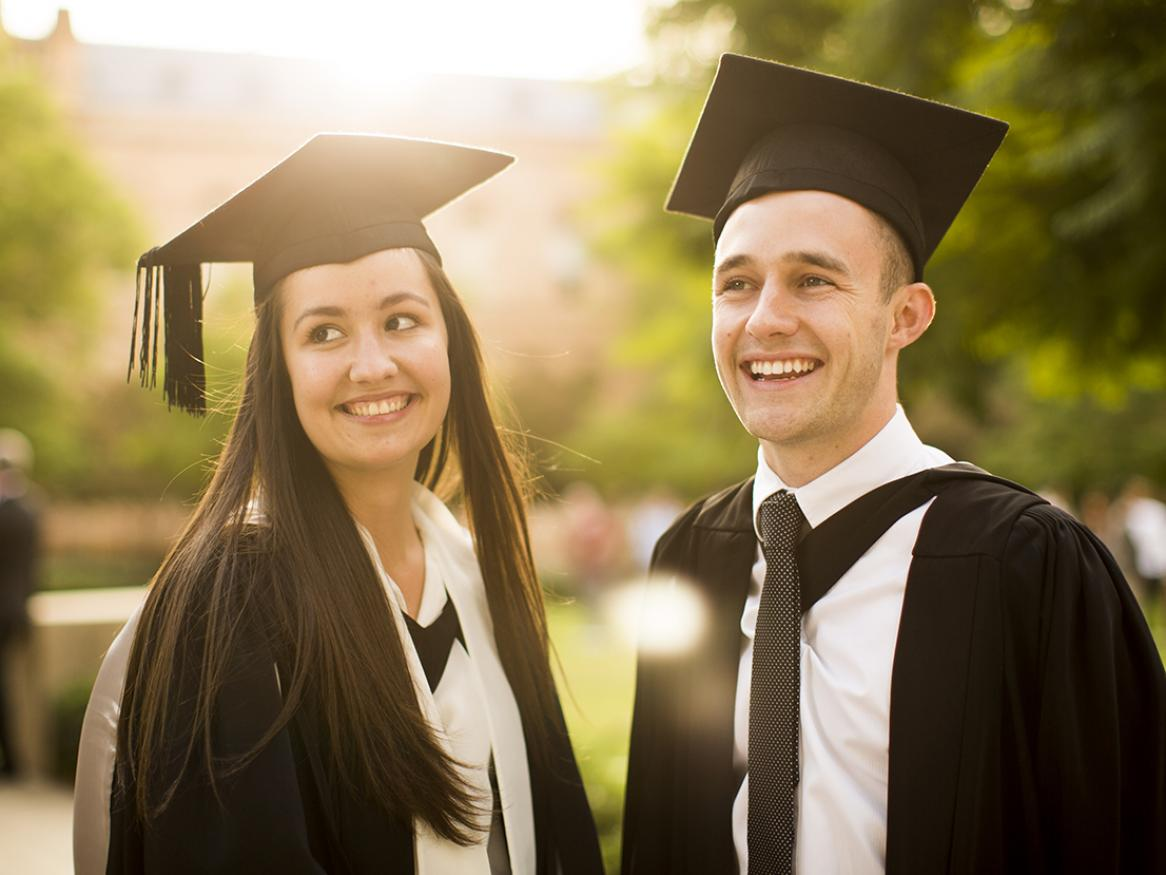 Photo of two very, very happy graduates in graduation gowns