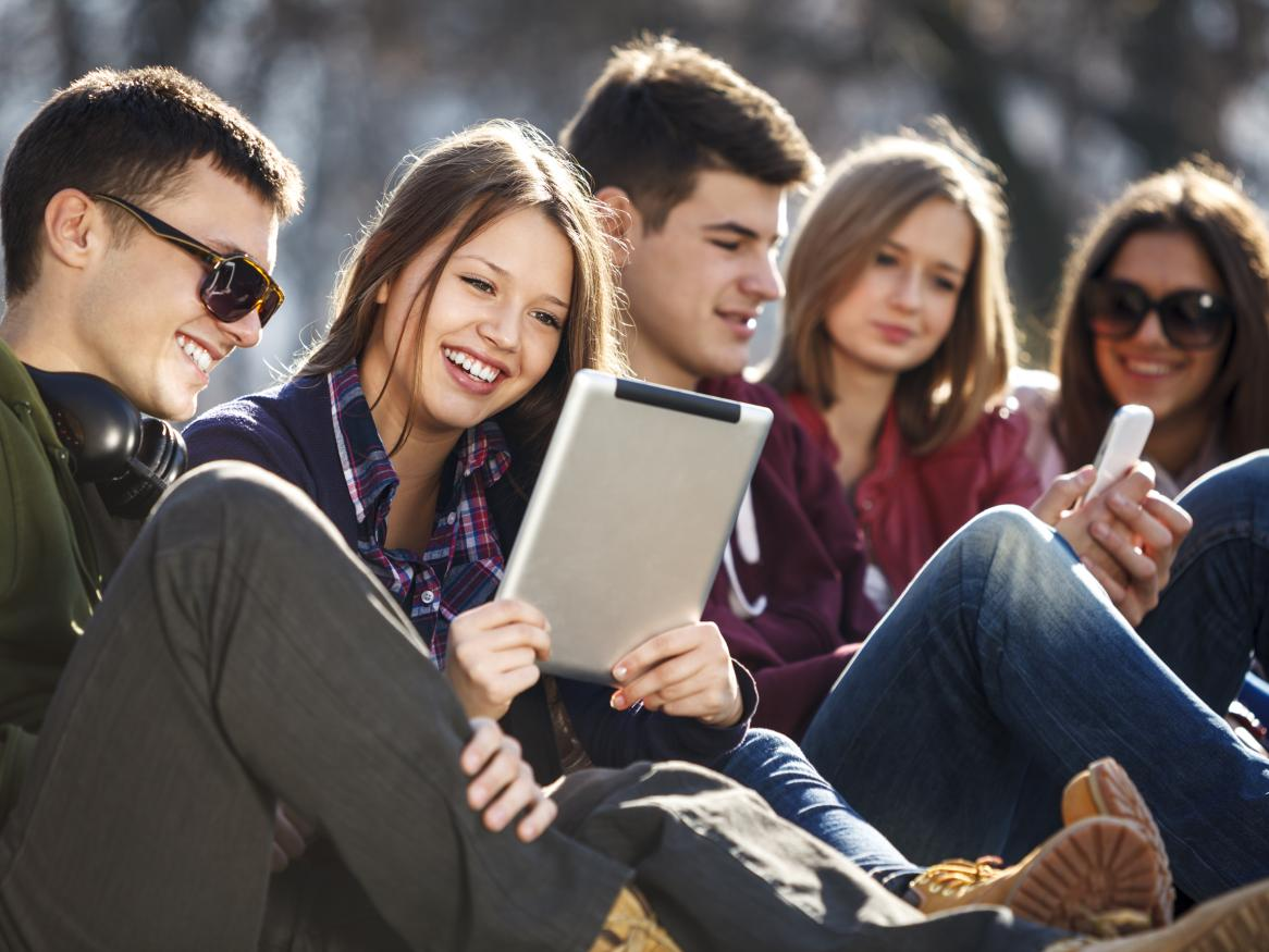 Photo of students sitting outside with iPad