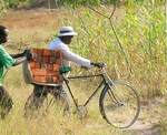 Donated bicycles are used to carry loads of bricks.