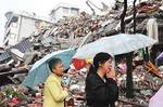 Two Chinese women weep in front of a collapsed building in Dujiangyan, in the Sichuan Province.
