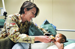 Colonel Susan Neuhaus (left) pictured with an Afghan patient during her tour of duty in the Oruzgan Province in 2009.