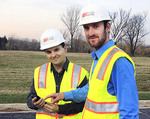 University of Adelaide graduate and Spectra QEST engineer Michael Howland (right) with one of his colleagues at United States company PSI, Anthony Brandonisio.  They are holding one of the handheld devices used for the many tests needed on the DFW Connector project.