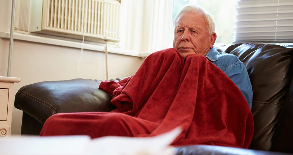 Elderly man keeping warm