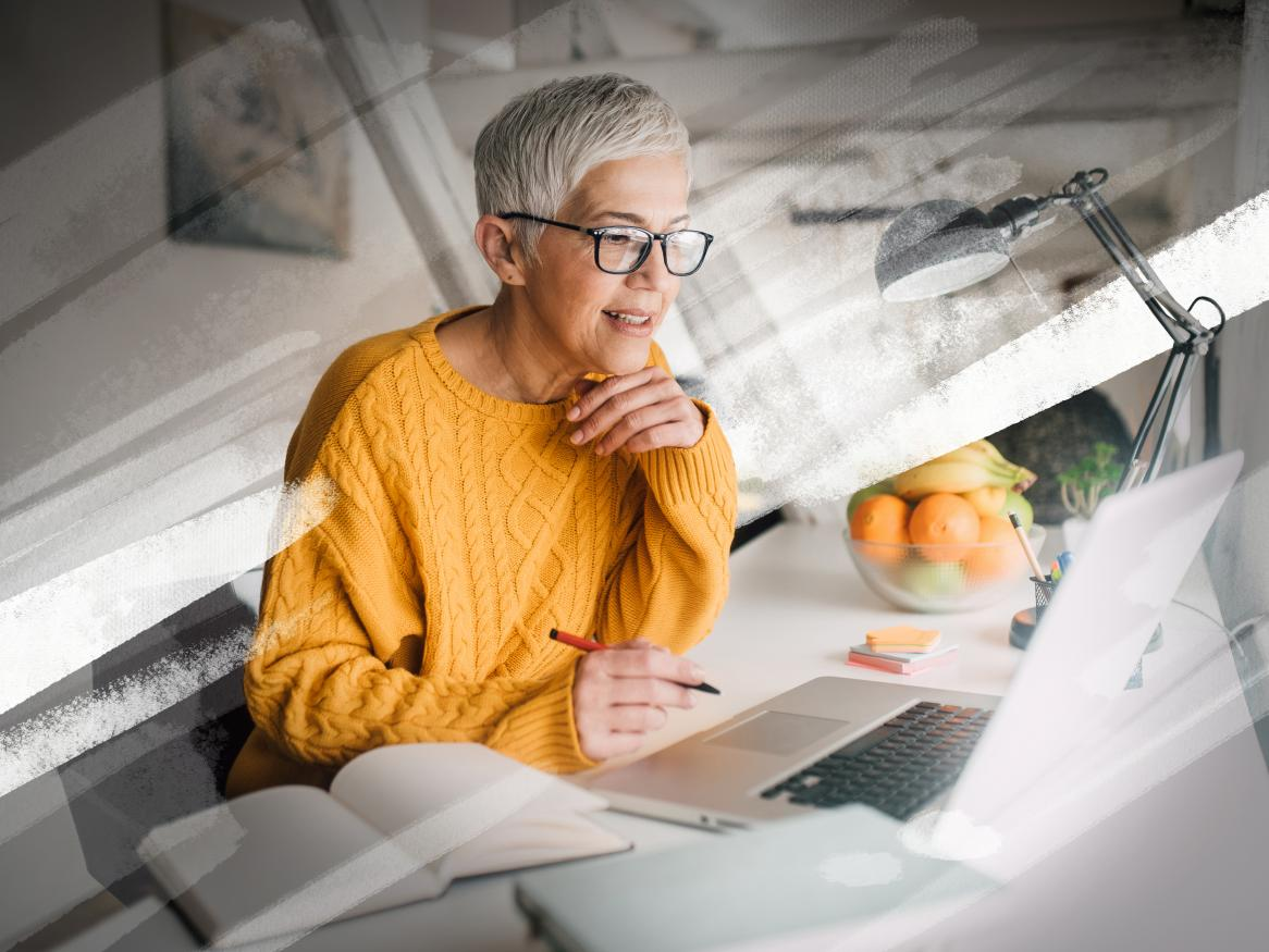 Mature lady sitting in front of a laptop with a pen in her hand