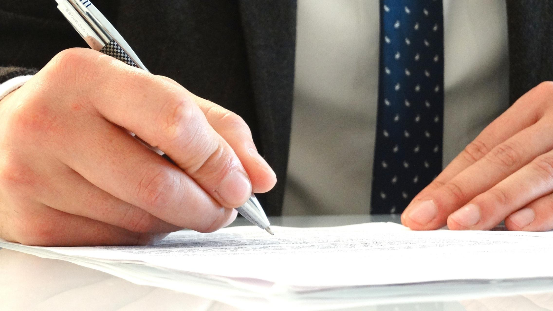 Close up photo of a person in a suit signing a document