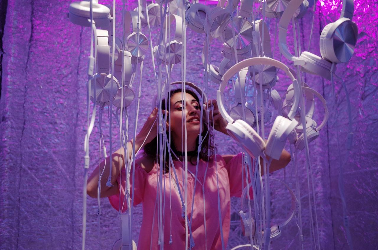 Woman standing in music installation with headphones