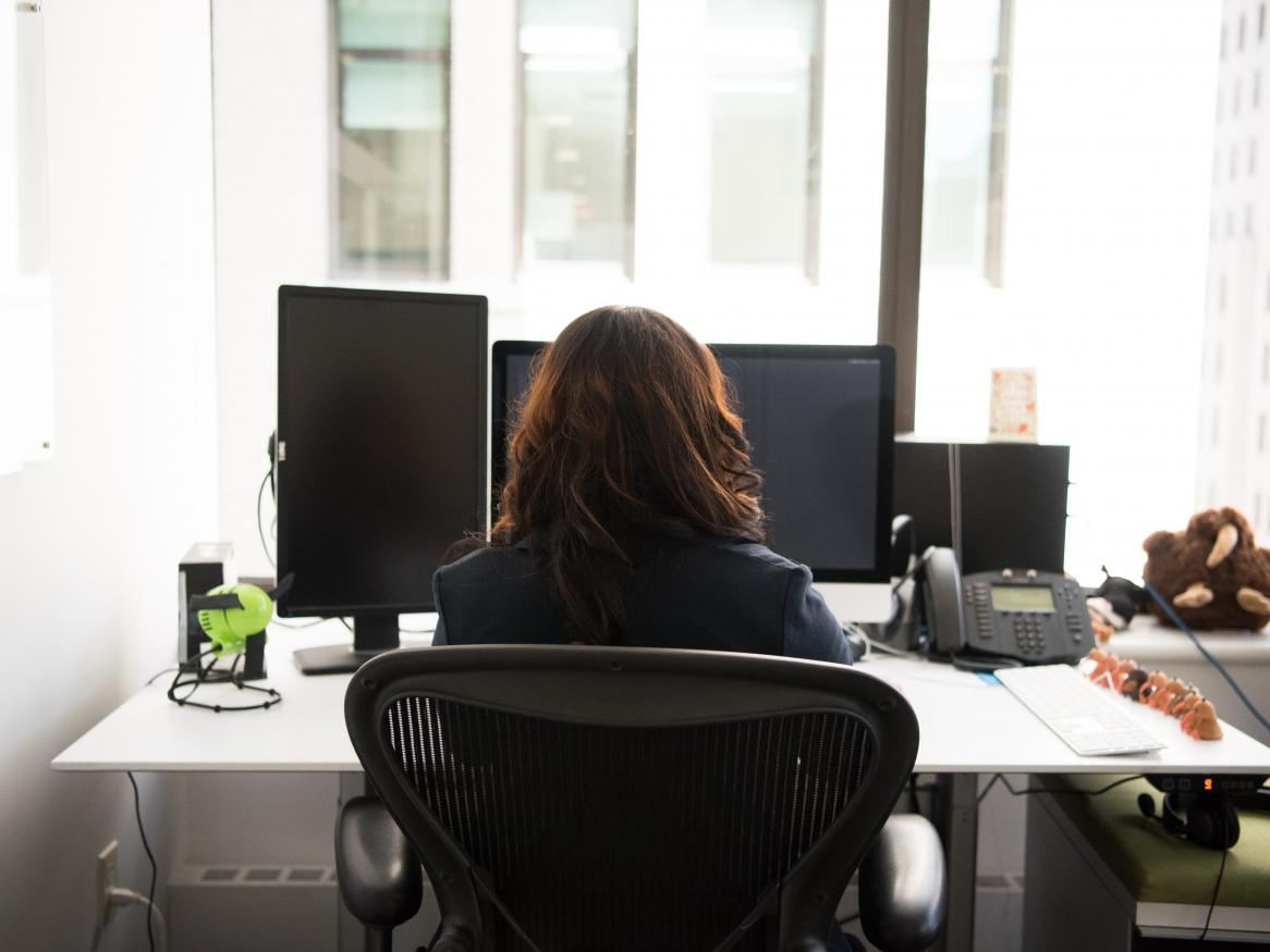 Picture of a woman sitting at a desk with a phone