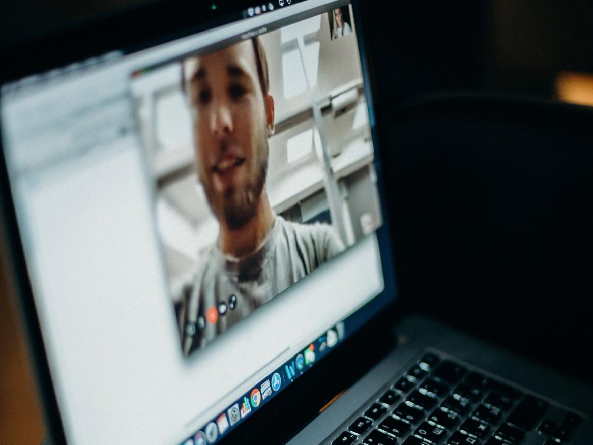 Person videoconferencing on laptop