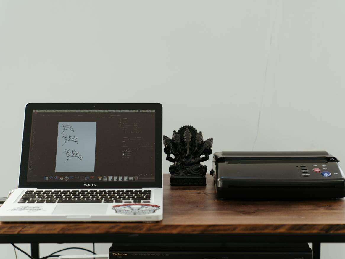 Mac laptop and printer on a desk at home