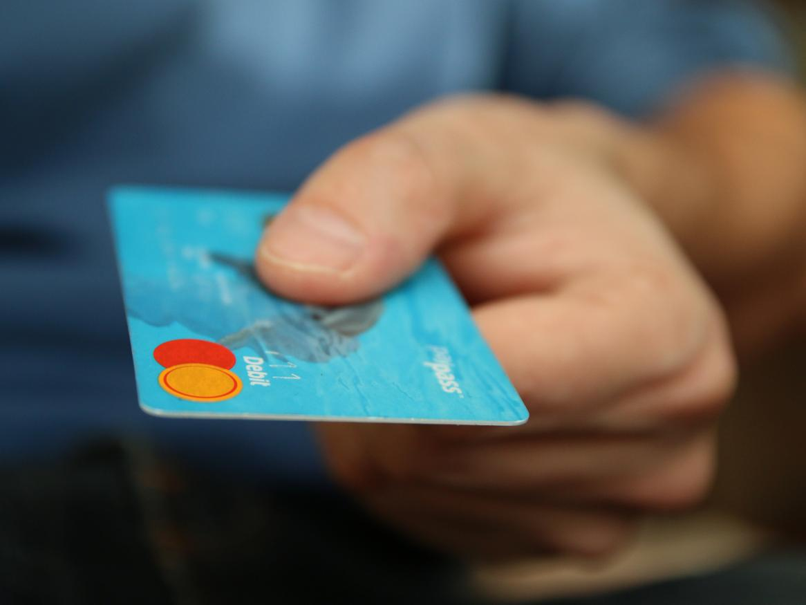 Man's hand holding out a credit card