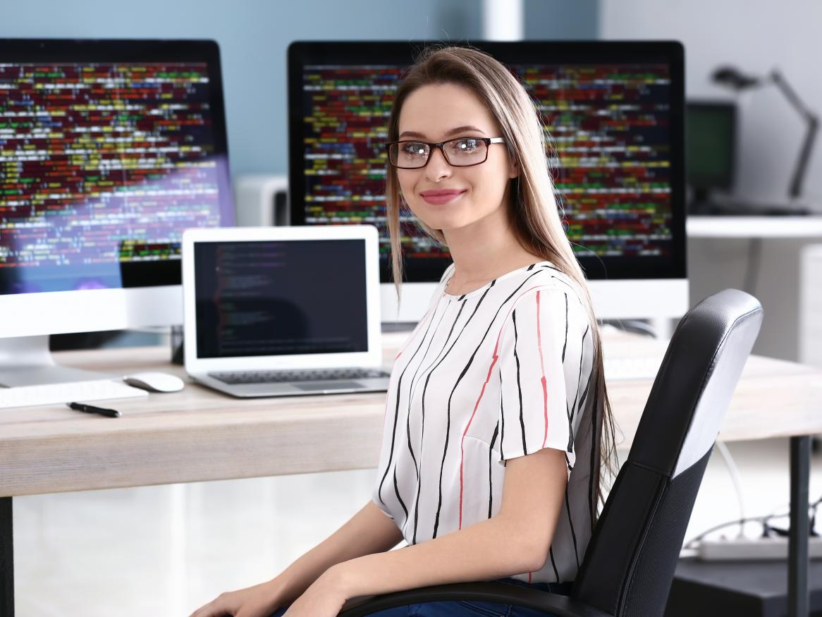A young woman sits at a desk by a laptop with coding screens in background